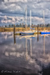 yacht moored to dock with reflection in water