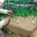An elderly person is making a rug