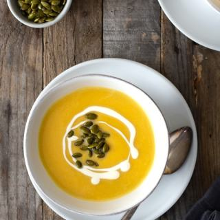 Overhead view of two bowls of creamy butternut squash soup topped with cream and pepitas in white bowls over a white plate with rustic spoons surrounded by a small bowl of pepitas and a dark dish towel on a rustic grey wood surface.