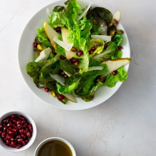Overhead shot of a Pear and Pomegranate Salad with Goat Cheese and Pistachios with lemon pomegranate dressing in a white bowl surrounded by small bowls of pomegranate arils and dressing on an off white textured surface.