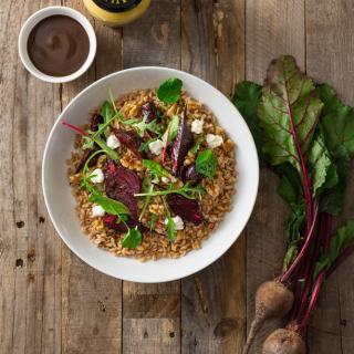 Overhead shot of a dish of farro topped with roasted beets, walnuts, goat cheese, and mixed greens (arugula, watercress, baby chard) with dijon balsamic vinaigrette surrounded by fresh beets with greens, a small bowl of dressing and a jar of Maille mustard on a rustic, grey wood surface.