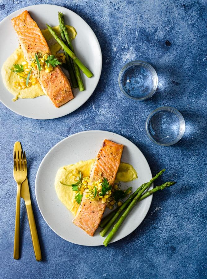 Overhead shot of two plates of miso butter salmon over corn puree topped with whole corn and mixed herbs, and served with asparagus. The plates are surrounded by gold utensils and water glasses on a blue textured surface.