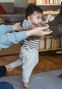 happy parents supporting baby making first steps
