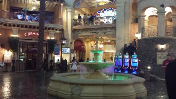 an interior photo of a fountain and shops, restaurants all around