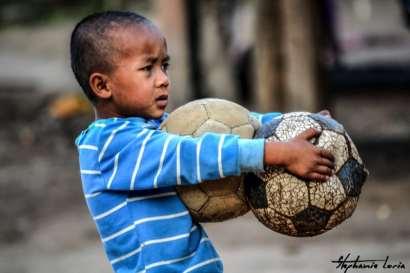 enfant thailandais avec deux ballons degonflés dans les mains