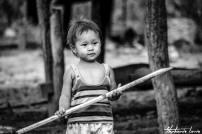 bebe thailandais tenant un baton en bois dans ses mains