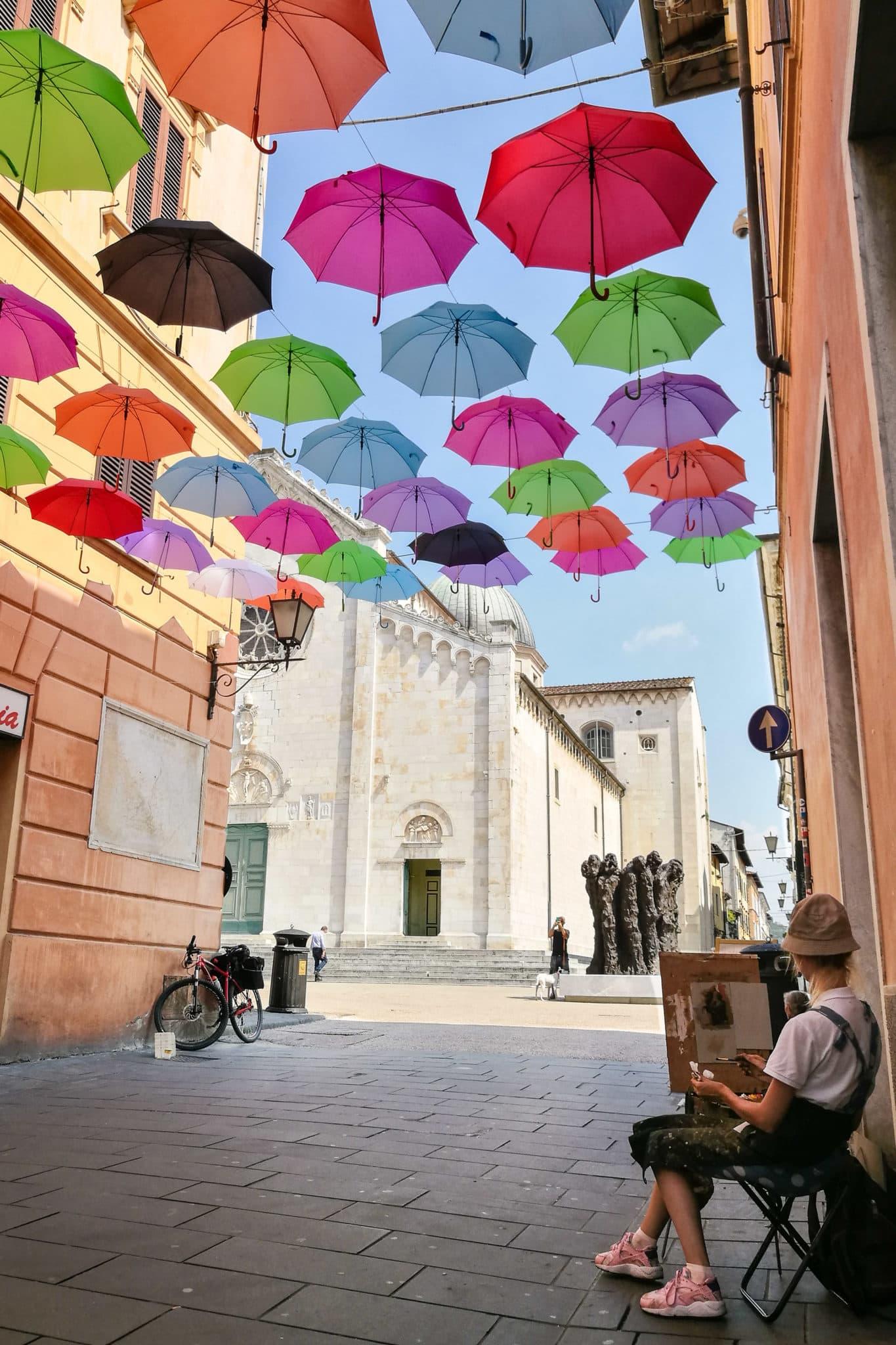 Painter under the floating umbrellas in Pietrasanta