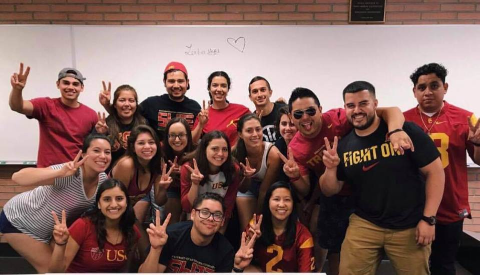 "Jose with the SHPE 2017-2018 leadership board, posing with the ""fight on"" hand motion, which resembles a peace sign."