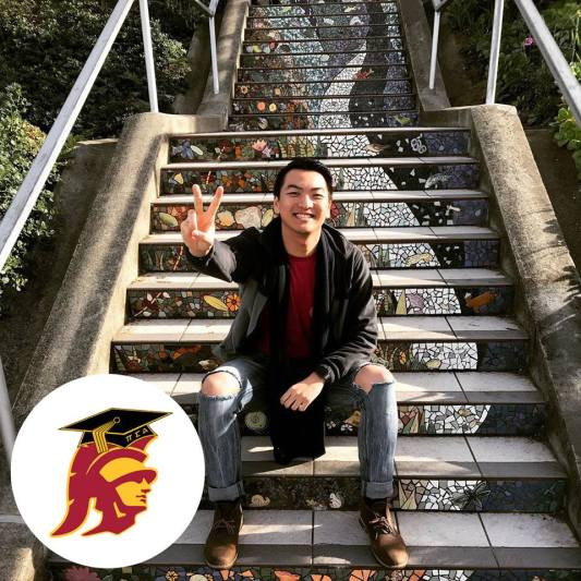 "Keck School of Medicine of USC student, aspiring doctor, Anson Tam, sitting on a stairway, holding up the USC ""Fight On!"""