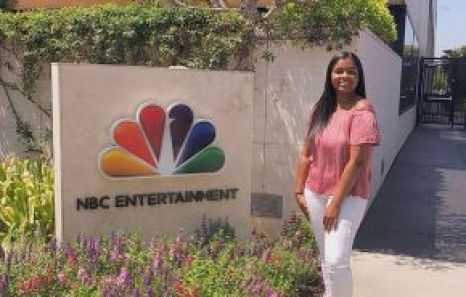 Briana Johnson, USC Marshall School grad, standing next to the NBC Entertainment sign at NBC Universal Studio lot.