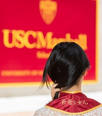 "A photograph of the back of Eugenia Huang, showcasing the stitching on her graduation stole, where it says, ""Her Father's Daughter"""