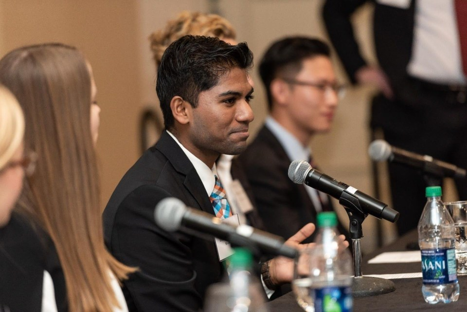 Eesen Sivapalan, transferring to USC Marshall School graduate, photographed sitting at a table next to students, wearing a business suit.