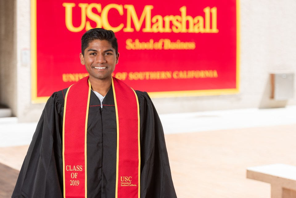 Eesen Sivapalan, transferring to USC Marshall School graduate, wearing graduation gown, standing in front of the USC Marashall School building.
