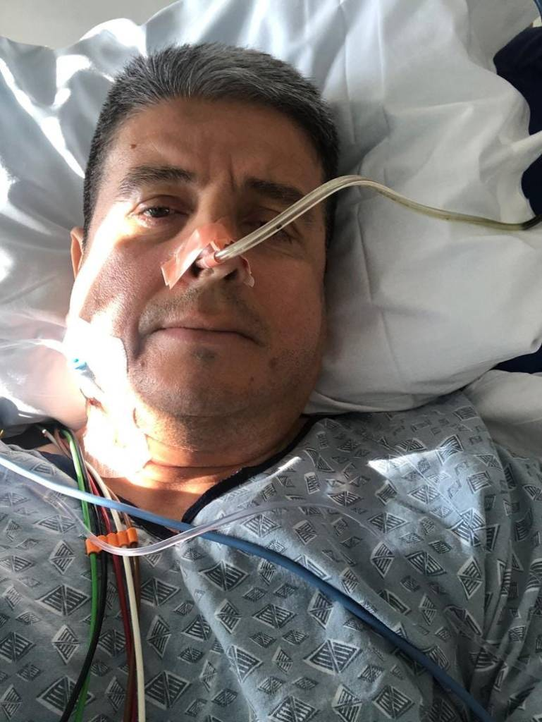 Tony Herrera photographed in a hospital bed in a selfie style photo. He was a medical tube inserted into his nose and is covered in life monitoring wires connected to medical equipment.