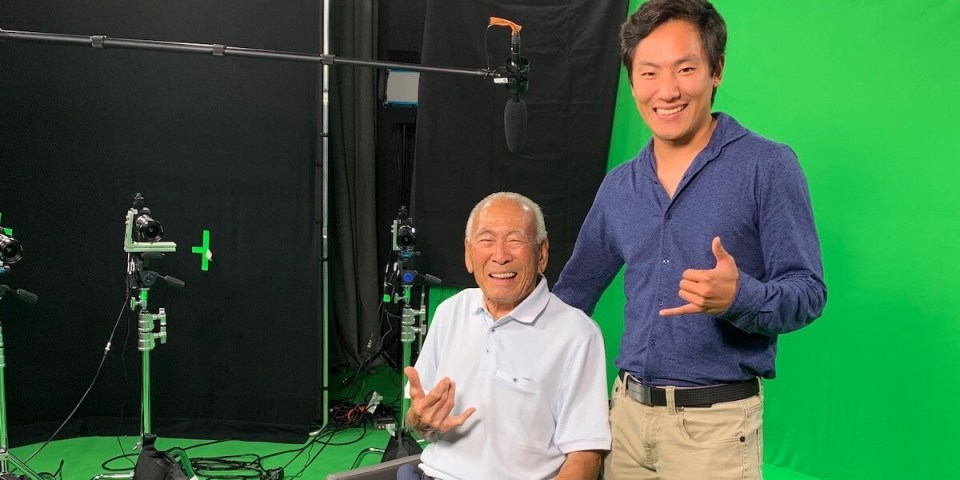 Cole and Japanese war vet Lawson Sakai are next to each other in a film studio with a green screen background behind them. They're embracing each other and giving a shaka sign with their hands.