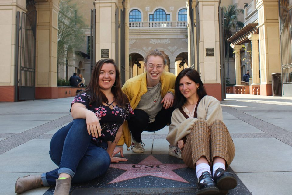Madison Holbrook USC student film screening. Madison on left, Ella harris in middle, and producer Caroline Quien on right huddled together in front of the USC SCA building.