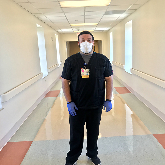 Christian Diaz, who helps patients, stands in the middle of a hospital hallway wearing scrubs and a face mask.