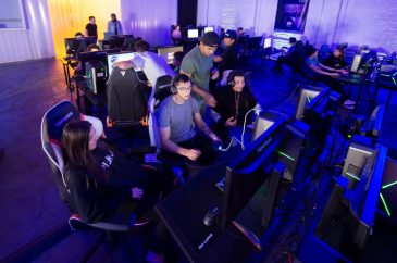 A group of men and women are huddled around computers playing games on them.