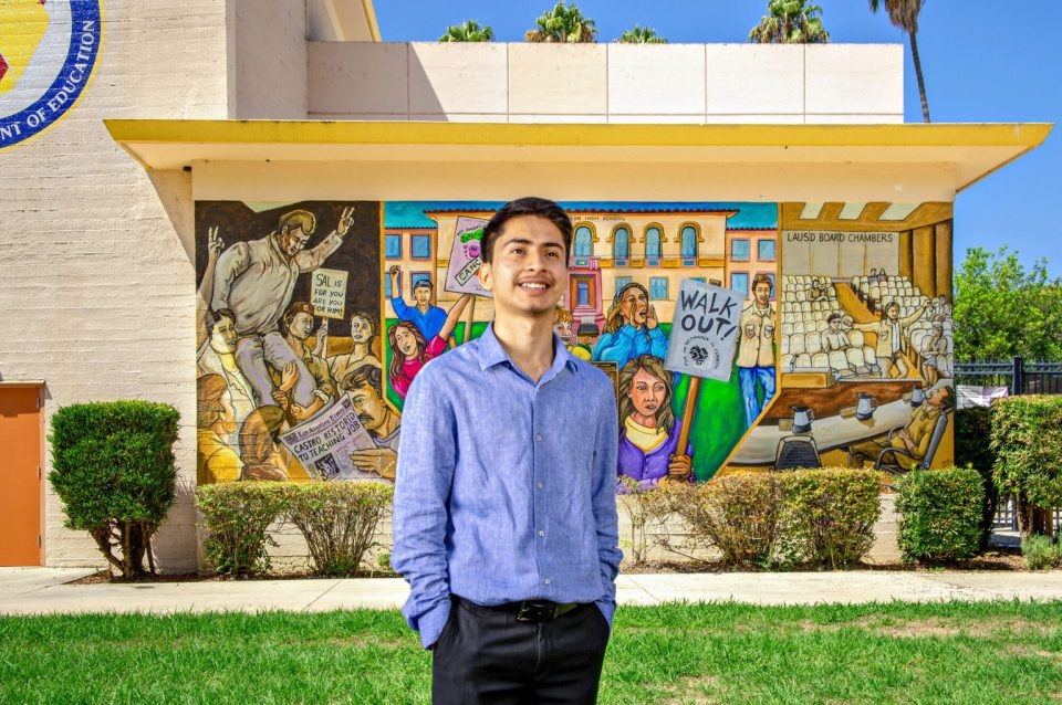 NAI scholar Ivan Garcia is posing in front of his middle school.