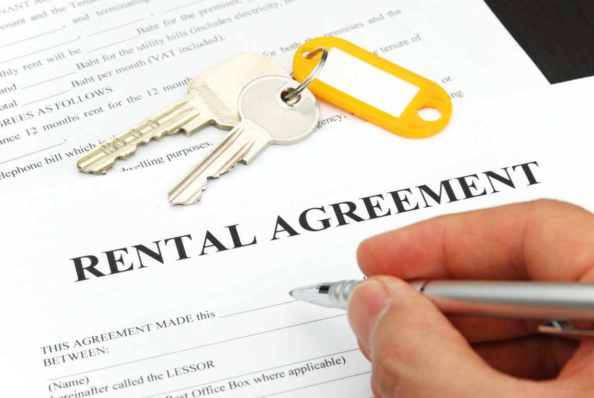 rental-agreement-form-with-signing-hand-and-keys-and-pen