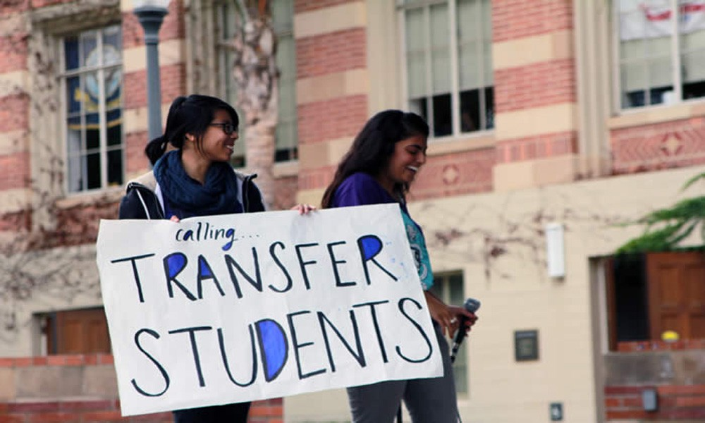 transfer student holding a sign