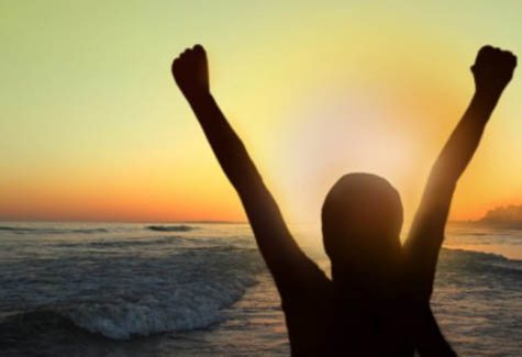 woman with her arms raised at the beach during sunset