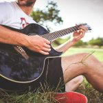 man sitting outside playing the guitar