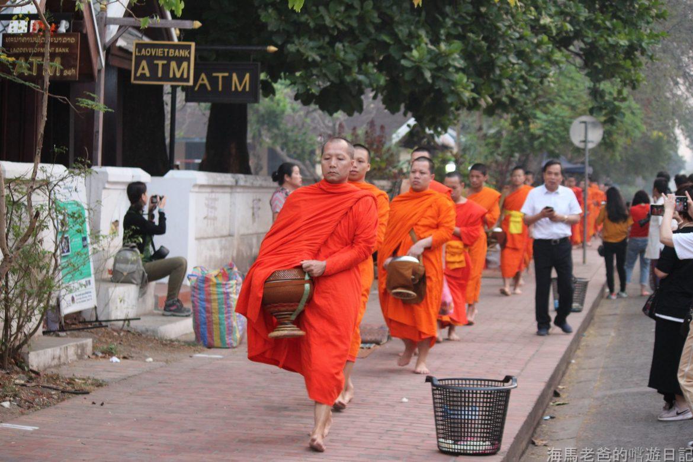 寮國旅遊|延續千年的善念,晨霧中踽踽而行的橘色身影