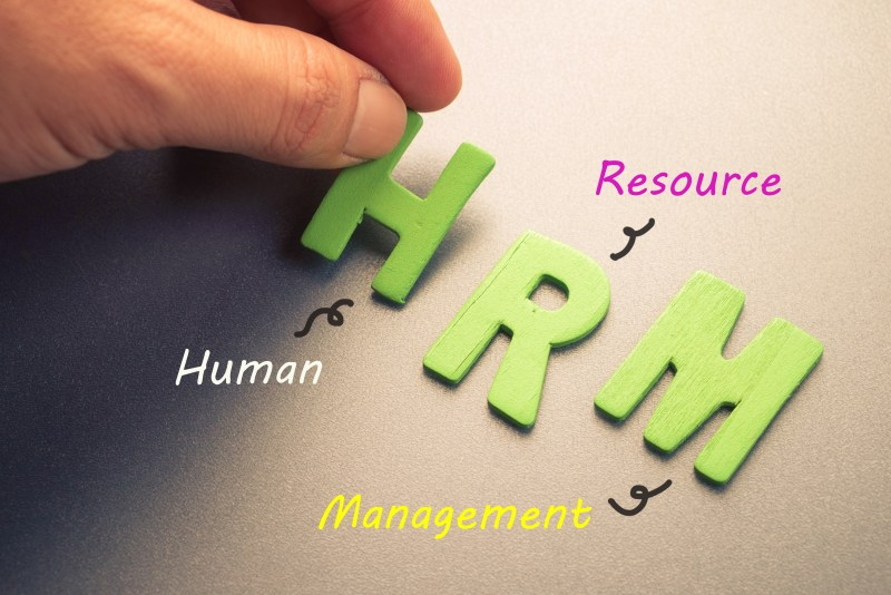 Hand arrange wood letters as HRM (Human Resource Management)