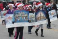 "A group of children march down the center of Elkhorn's North Wisconsin Street displaying artist Jan Castle Reed's Christmas Cards during the 2012 Christmas Card Town Parade. Reed was commissioned for 14 years to paint the Christmas cards, reviving the tradition of artist Cecile Johnson, whose six watercolor paintings for Ford Motor Company in 1958 earned the city it's ""Christmas Card Town"" title."