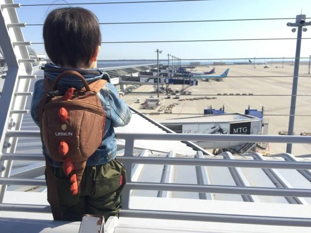 子供が飛行機を眺める後ろ姿