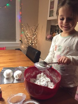 Scooping the ingredients into the bath bomb molds - childs play