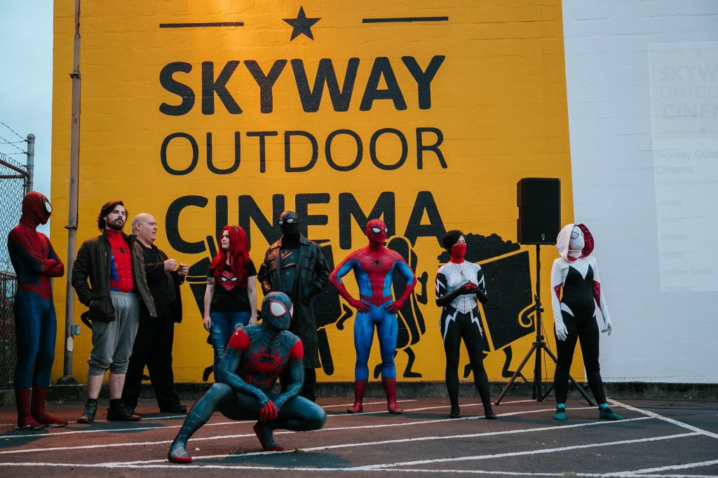 Skyway Outdoor Cinema 2019 - Spider-Verse - Spider-Man Characters Assembled in Front of Wall - Hallie McGee Photography