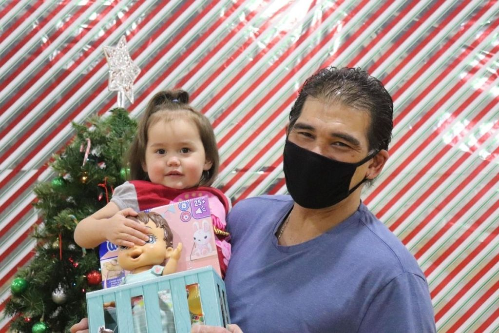 Parent holds small child with babydoll toy in front of a Christmas tree. Photo courtesy of REACH.
