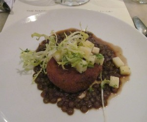 Stuffed pigs trotter round on bed of lentils