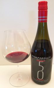 50th Parallel Estate Pinot Noir 2015 with wine in glass