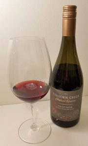 Tinhorn Creek Vineyards Oldfield Reserve Pinot Noir 2014 with wine in glass