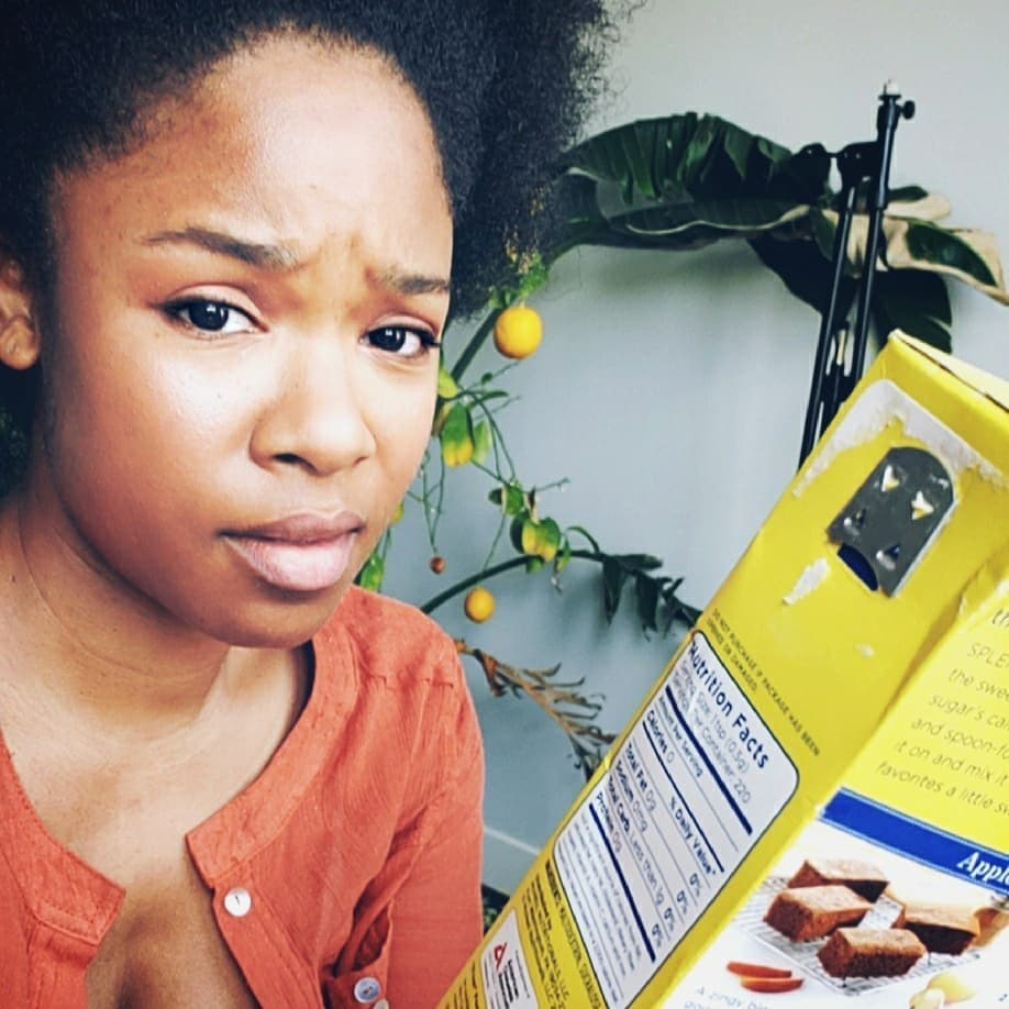 perplexed woman staring at boxed food label