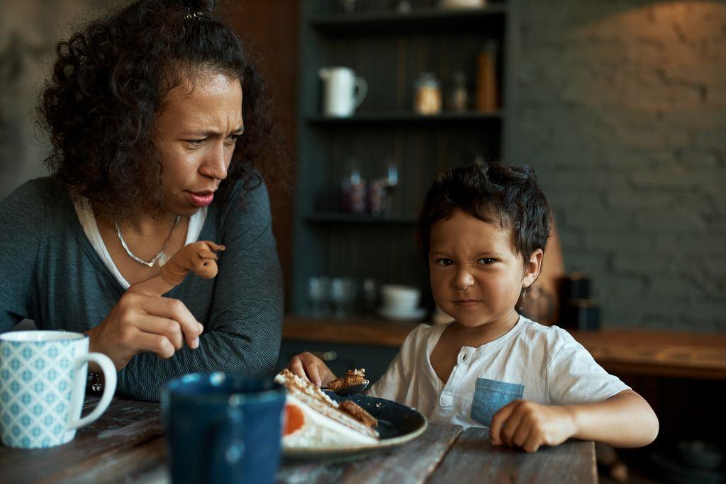 طفل تقنعه والدته بالأكل.