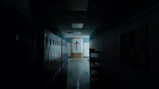 Das Foto zeigt einen Schulkorridor und am Ende ein Jesuskreuz an der Wand. Foto gewählt um zu zeigen, dass Outlast 2 religiöser inszeniert.