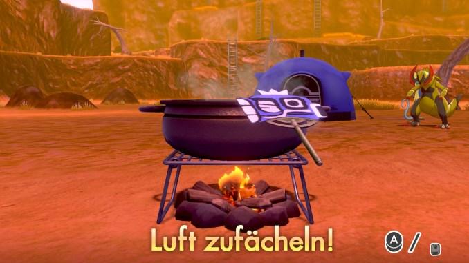 Das Foto zeigt einen Kessel über einer Feuerstelle und einen Fächer.