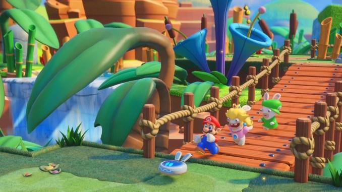 Das Foto zeigt Mario, Rabbid Peach und Rabbid Luigi samt Begleiter über eine Holzbrücke rennen.