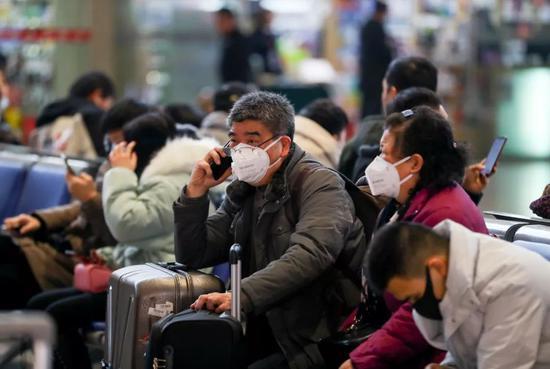 1月21日,武汉火车站候车大厅,戴着口罩的旅客在候车。(中新社供图)