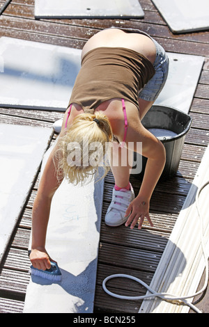 Woman cleaning the floor with a scrubbing brush besides a