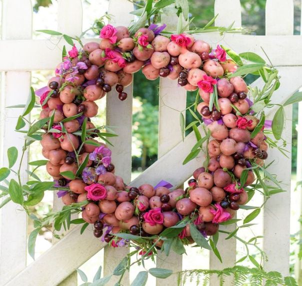 This wreath is made of potatoes, cherries, roses, and vines.