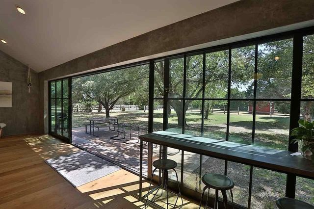 The property is visible through walls of floor to ceiling windows and glass doors.