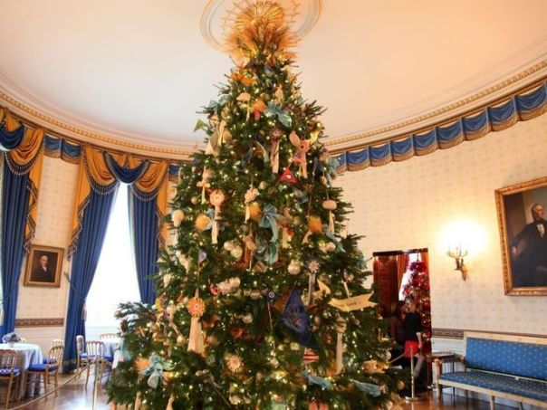 "This Blue Room tree featured sheaves of wheat and handmade ornaments to carry out that year's theme of ""Simple Gifts."""