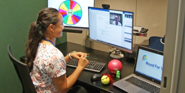health professional looking computer screen engaging in teleconference