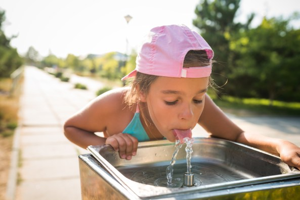 Aboriginal toddler drinking from the water fountain in the summertime