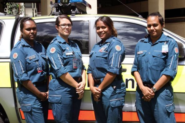 four Aboriginal female paramedics standing in front on an ambulance